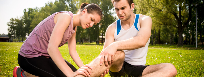 Woman is helping to young man with injured leg from sport activity